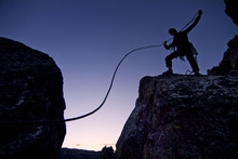 Silhouette Of Climber Standing On Rock