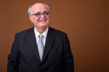 Overweight Senior Businessman Wearing Eyeglasses Against Brown B