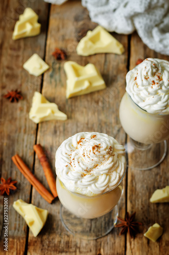 Hot white chocolate with whipped cream and cinnamon on a wood background