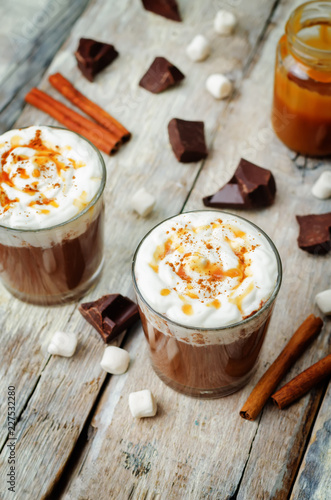 Dark hot chocolate with whipped cream and salted caramel sauce on a wood background