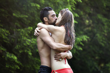 Couple Embracing While Kissing...