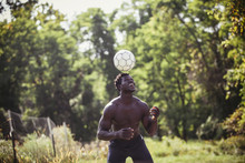 Man Holding Soccer Ball On Head At Sunny Day