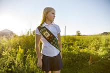 Thoughtful Schoolgirl In Sash Standing On Field