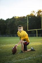 Boy With American Football Kne...