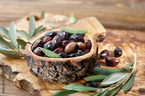 Fresh brown kalamata olives and olive tree leaves in authentic greek wooden bowl with bark, close up view