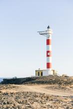 Lighthouse On Shoreline In Sunlight
