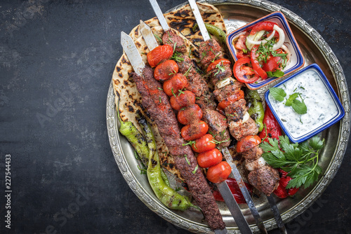 Traditional oriental Adana kebap and shashlik skewer with tomato and flatbread as top view on a plate with copy space left