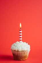 Birthday Cupcake With Striped Candle On A Red Background