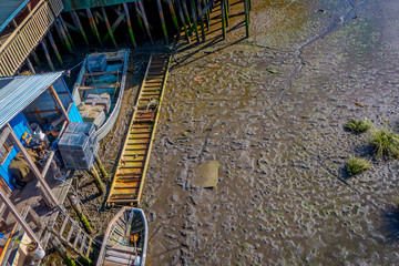 Above view of single boat next to wooden buildings on stilts palafitos in Castro, Chiloe Island, Patagonia