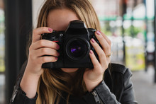 Young Woman Holding Large Camera
