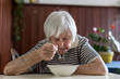 Solitary senior woman eating her lunch at retirement home. Social aid for retirement citizens concept.