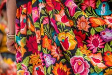 Mujer Latina Con Pulsera De Oro Y Falda Oaxaqueña Del Istmo De Tehuantepec Bordada Con Flores Multicolores, Bailando En La Guelaguetza De Oaxaca Mexico