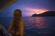 A asian woman standing on the yacht deck and watching the twilight sea