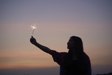 Silhouette Of Woman Holding Up A Sparkler