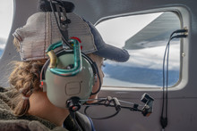 Female Passenger Looks Out The Window While Flying In An Alaskan Bush Plane, Wearing A Headset