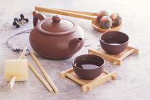 Traditional Chinese Tea Cups, Ceramic Teapot And Tea Ceremony Attributes Are On A Gray Table.