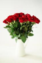 Red Roses In A Pitcher. Tilt-shift Effect.