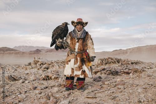 Hunter holding eagle on landscape