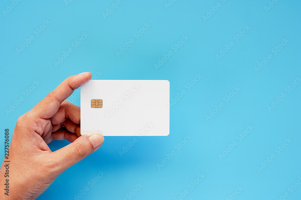 Fototapeta Hand holding blank credit chip card on blue background for business and finance concept