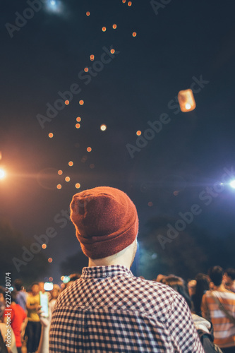 Festival time - Man with hat looking at fire lanterns in the sky during the night