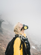 Young Woman In Mask On Volcano Crater