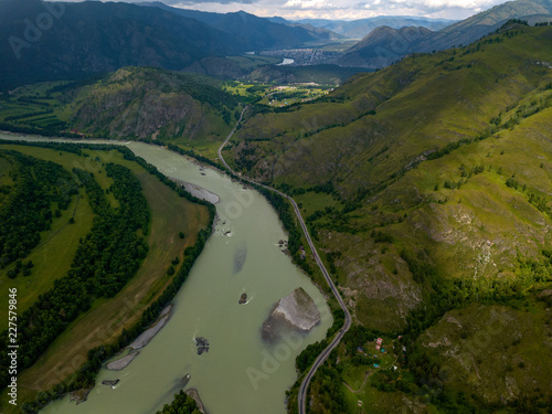 Aerial view of the nature of the Altai Mountains during an approaching thunderstorm with clouds and, as yet, a bright shining on the village at the foot of the mountain with a green meandering river