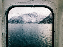Norwegian Fjord During Winter Shot Through Wet Ferry Window