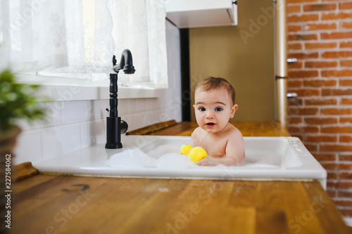Baby having a bath in the kitchen sink