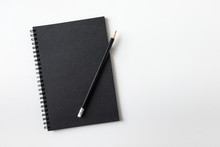 Top View Of Notebook Black Cover With Pencil On White Desk Background