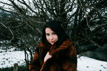 Portrait Of A Beautiful Woman Wearing A Fur Coat In A Winter Landscape With A Tree Behind Her