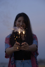 Happy Young Woman Playing With Sparklers
