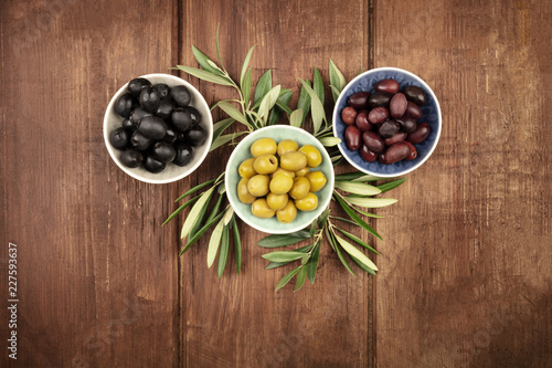 Various olives in bowls with leaves, shot from the top on a dark wooden background with a place for text