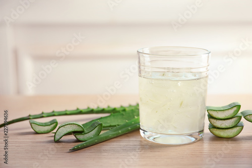 Glass of aloe vera juice and green leaves on wooden table against light background with space for text