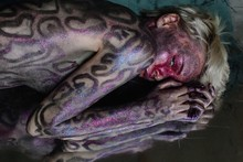 Young Woman With Shiny Snake Bodyart Laying On Reflecting Floor
