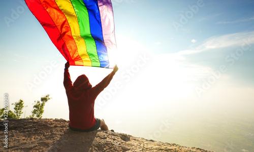 фотография man sitting on mountain top waving rainbow LGBT symbol flag in bright sunlight b