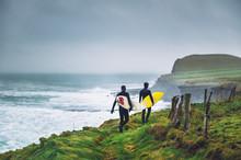 Surfers Walking On The Cliff Near Ocean