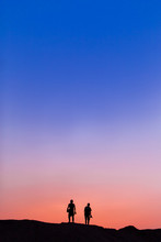 Two People On The Top Of Mountain In Sunset