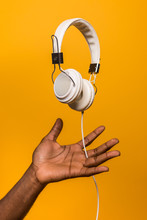 Concept Shot Of Black Man Doing Balance With Suspended Headphone