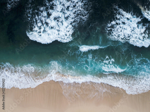 Top view: ocean waves washing sand coastline