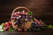 Ripe Grapes In Wicker Basket On Wooden Background.