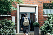 A Tourist Goes To The Guesthouse Or Hostel In Order To Stay In A Room That He Booked Or A Student With A Backpack Returns Home After His Studies At The Institute Or On Vacation.