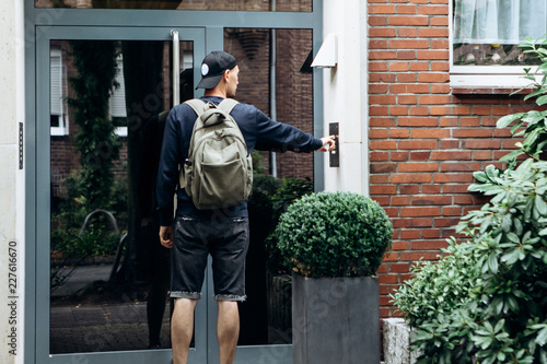 The tourist rings the doorbell to check in to the room he has booked or the student with the backpack returns home after classes at the institute or on vacation Canvas Print
