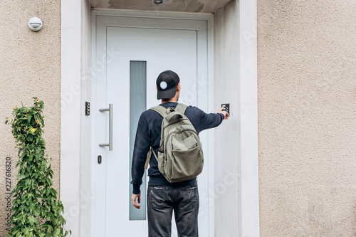 Fototapeta The tourist rings the doorbell to check in to the room he has booked or the student with the backpack returns home after classes at the institute or on vacation