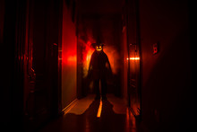 Halloween Concept. Creepy Silhouette In The Dark Corridor With Pumpkin Head. Toned Light With Fog On Background. Selective Focus