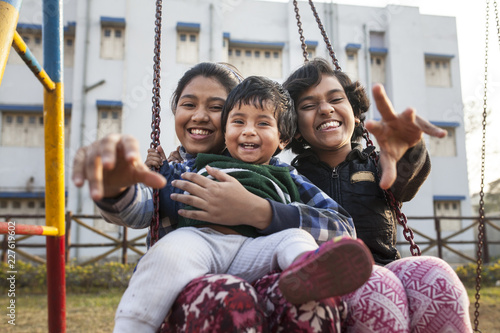Three Sisters making fun and laughing sitting on a swing