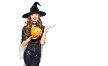 Halloween. Sexy Witch With Bright Holiday Makeup. Beautiful Young Woman In Witches Costume With Pumpkin Lantern Pointing Hand, Showing Product Over White Background