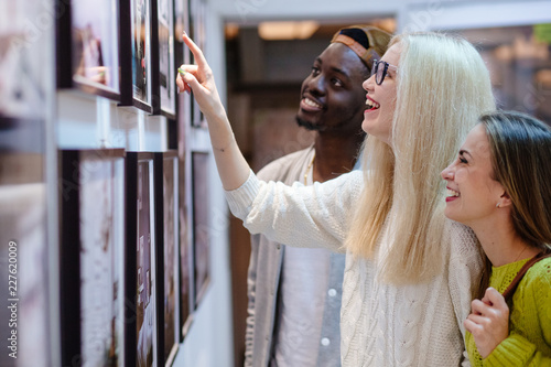 Three young people hipster students with different skins looking happy together, talkng, looking at picture on wall, spending free time together in art photo gallery. Multi ethnic, friendship concept.