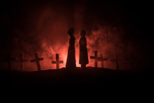 Halloween. Scary Zombie Bride On A Night Cemetery Holds A Pumpkin Lantern.