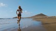 Fitness runner woman running on beach listening to music motivation with phone case sport armband strap. Sporty athlete training cardio barefoot with determination under summer sun.