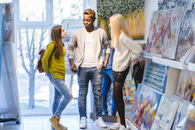 Full Height Portrait Of Three Multi Ethnic People Students At Indoor Art Exhibition Arround A Framed Work, Talking. Young Friendly Black Skinned Guy Between Two European Appearance Girls Friends.